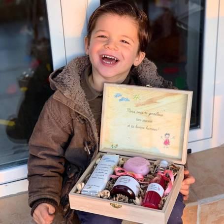 Un garçon tient une boîte en bois pour cadeau de fêtes de meres contenant 4 souvenirs