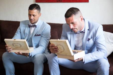 Deux hommes tiennent boîte en bois pour cadeau de témoin de mariage