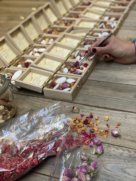 une main en train de remplir les mini box avec dragées aux amandes et fleurs sèches