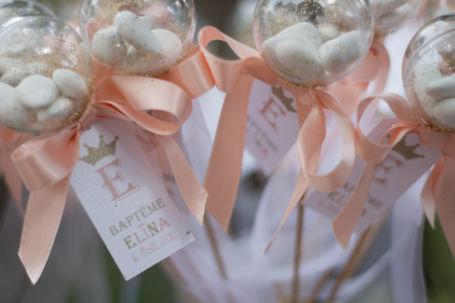 quatre sucettes à dragées avec ruban couleur pêche pour cadeau d'invite d'un baptême
