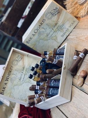 box bar à cigares ouverte avec plusieurs bouteilles de whiskey jack da daniel's et cigares