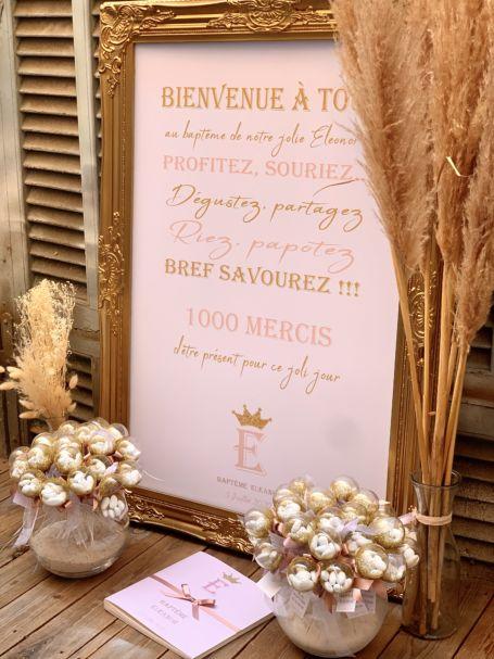 panneau de bienvenue sur table d'entrée pour cérémonie de baptême avec deux bouquets de sucettes