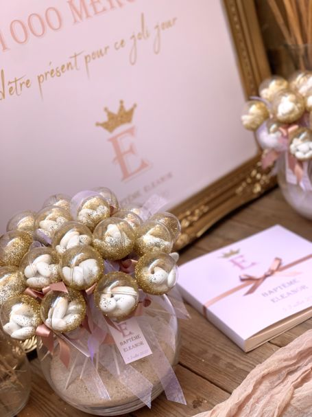 détail décoration de table d'entrée pour cérémonie de baptême avec deux bouquets de sucettes, panneau de bienvenue et livre d'or