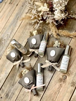 quatre kit cadeau d'invité contenant un pochon de fleurs sèches et un mini parfum