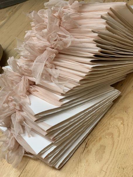 une pile de livrets de messes de mariage avec lacets en organza