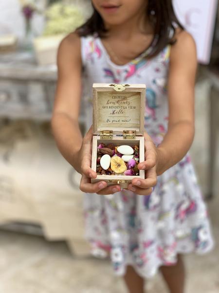 jeune fille tient une petites boîte à dragée pour cadeau d'invité