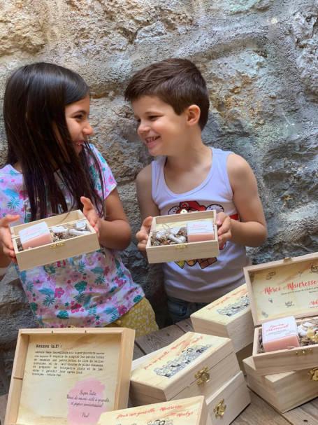 deux enfants tiennent des coffrets cadeau pour nounou