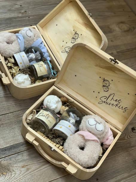 deux coffrets cadeau de naissance avec ses cadeaux : doudou, boule à neige, savon et boîte à dents